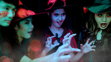 Young teens, men and women Celebrating parties in evening gowns, drinking, taking pictures, dancing and pretending to be ghosts. Looking at the camera with a smile while celebrating Halloween