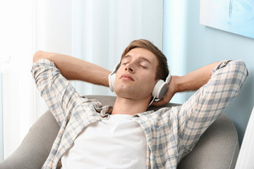 Handsome young man relaxing and listening to music at home