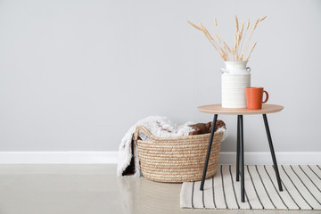 Table and wicker basket with plaid near light wall