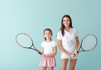 Little girl and her mother with tennis rackets on color background