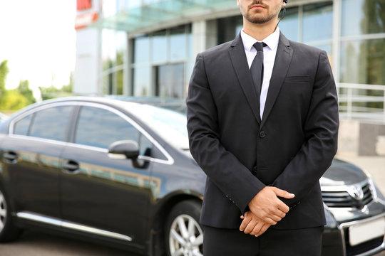 Professional bodyguard near car outdoors