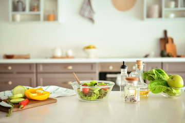 Bowl with salad and ingredients on kitchen table