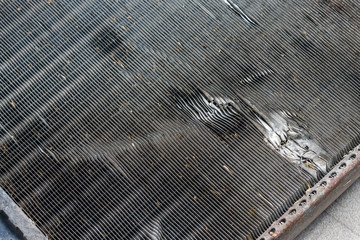 The surface of the car cooling radiator with marks of impacts by stones on a road