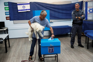 A man holds his dog as he casts his vote in a ballot box during Israel's parliamentary election at a polling station in Rosh Ha'ayin, Israel
