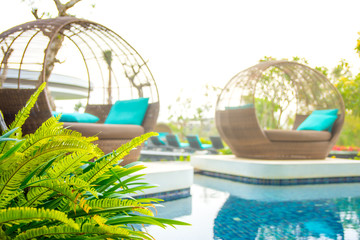 Close up poolside image with daybeds overlooking pool and a backlit morning glow