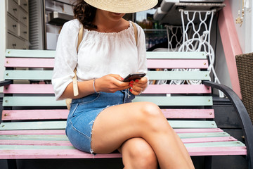 Content woman in hat using smartphone while sitting on street