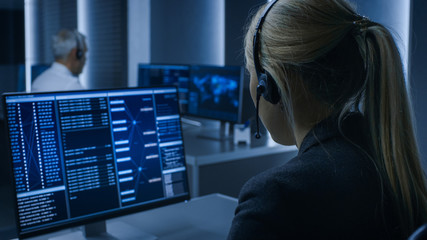 Back View of the Female Controller wearing Headset Working on Personal Computer, Monitoring Processes in the System Control Room full of Special Intelligence Agents. Wall mural