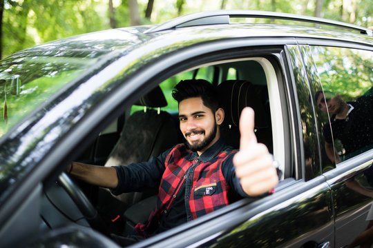 Attractive young indian man sitting in his car with thumb up smiling at the camera