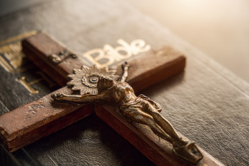 Closeup of wooden Christian cross on Bible, vintage tone. Symbol of God and goodness.