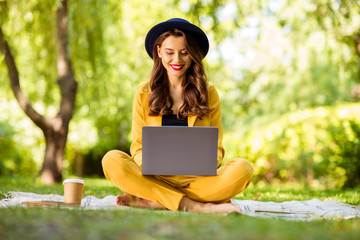 Fototapete - Portrait of her she nice-looking attractive lovely charming winsome trendy pretty cheerful cheery wavy-haired girl sitting in lotus pose typing on laptop in green park outdoors