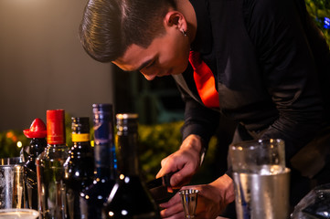 Spoed Foto op Canvas Professional bartender preparing fresh juice cocktail in drinking wine glass with ice at night bar clubbing counter. Occupation and people lifestyles concept. Outdoor and nightclub background