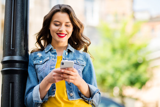 Close-up portrait of her she nice attractive lovely charming cute cheerful cheery wavy-haired girl in jeans denim using cell 5g chatting modern technology in downtown center outdoor