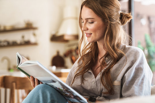 Positive optimistic redhead woman indoors sitting at home reading book or magazine.