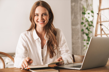 Pretty business woman using laptop computer holding notebook.