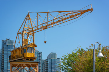 Old yellow vintage industrial loading crane on Granville Island, Vancouver, British Columbia, Canada