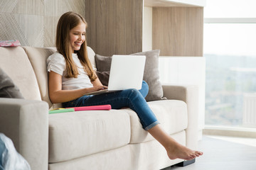 Smiling school girl sit with laptop at white couch