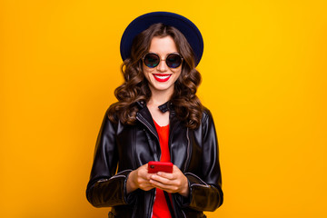 Fototapete - Portrait of charming cheerful positive girl use her cellphone comment text blog post wear black leather jacket isolated yellow color background