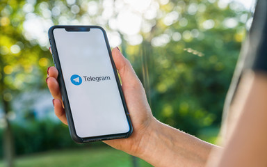 BERLIN, GERMANY AUGUST 2019: Woman hand holding iphone Xs with logo of Telegram application. Telegram app icon. Telegram is an online social media network. Social media app