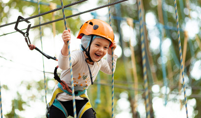 In de dag Amusementspark Little girl in helmet climbs ropes in adventure park outdoors. Extreme sport, active leisure on nature.
