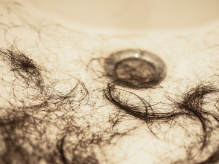 Close up of black hair on the sink - after cutting hair