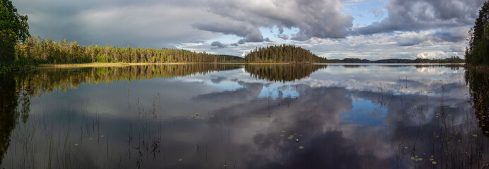 Inspirational panoramic view of lakes in which is reflected the cloudy sky and the wood on shore in the Finnish Karelia.