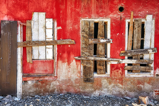 Abandoned shanty house with red wall and three windows barred shut with wooden planks