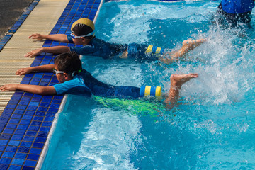 2 little duo boy age 5 and 8 years old lying prone at edge of pool and using legs kicking water for learning to swim with adult male swimmer and trainer in the blue swimming pool background.
