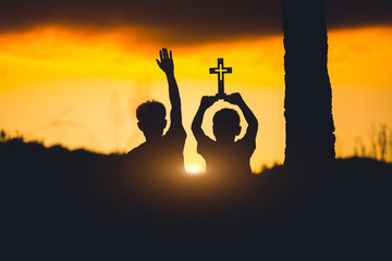 Silhouette of two young christian with cross ,christian concept.
