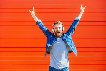 Cool trendy funny beard man in headphones listening music and showing rock gesture on red background.