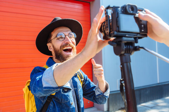 social media influencer creating content. man shooting video of himself using camera on tripod. smiling bearded hipster guy communicating with subscribers.