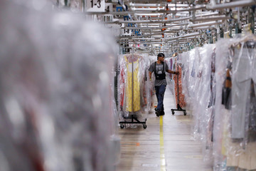 "A man moves clothing at Rent the Runway's ""Dream Fulfillment Center"" in Secaucus, New Jersey"