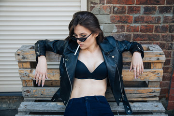 young girl in a leather jacket smokes cigarettes, rock style, cheeky and cute girl street posing style, rock punk lifestyle