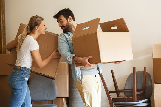 Young married couple moving into new home.They unpacking and cleaning .