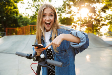 Smiling cheerful teenage girl in park walking on scooter using mobile phone.