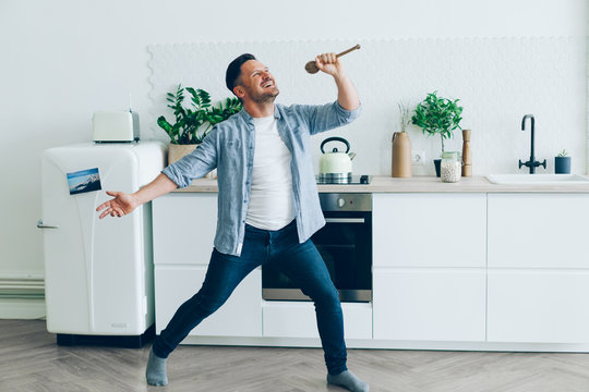 Portrait of playful middle-aged man singing in spoon in kitchen having fun standing in room alone holding kitchenware. People, happiness and lifestyle concept.