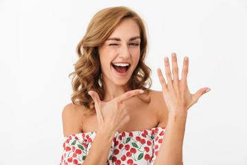 Image of a cheerful positive young woman posing isolated over white wall background pointing to her hand.
