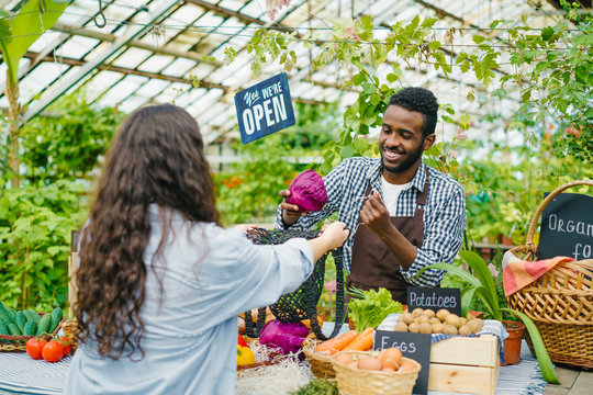 Female customer buying organic food vegetables cabbage in farm market while African American man salesperson putting products in bag. People and shopping concept.