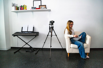 Girl reads book sitting in chair near camera