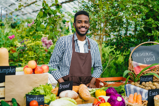 Portrait of handsome African American guy farmer standing in farm market smiling looking at camera waiting for customers. People, greenhouse and business concept.