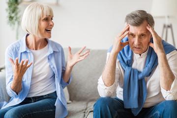 Angry senior woman shouting at upset man at home
