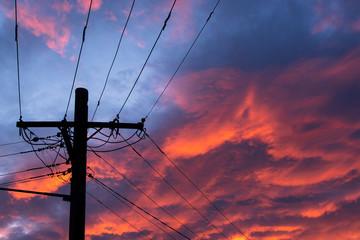 Electricity pole with purple cloudy sky.