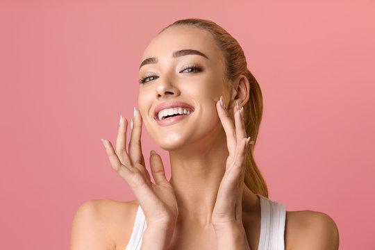 Portrait of beautiful woman touching skin or applying cream