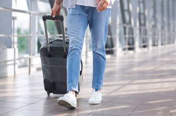 Man walking with suitcase in airport corridor