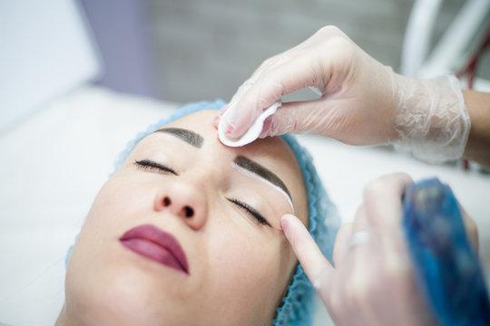 Decorative cosmetology. Eyebrow design. Closeup portrait of female client enjoying beauty procedure.