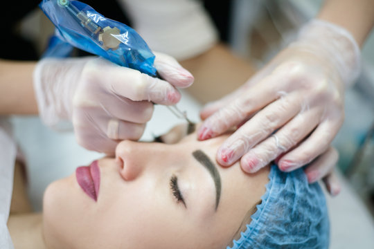 Eyebrow microblading. Closeup of lady having face beauty procedure in modern clinic.
