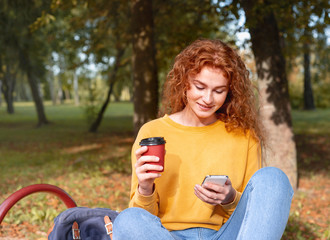 Smiling happy red hair student girl having a break with coffee outside in autumn park