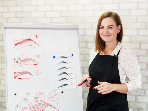 Permanent makeup courses. Successful female artist standing at white board with eyebrow sketches, telling about new techniques.