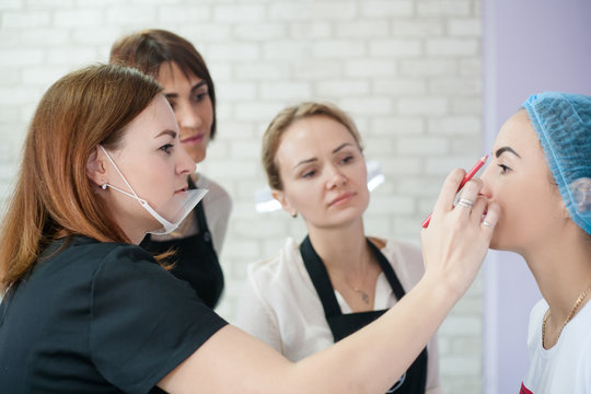 Modern decorative cosmetology class. Female beautician showing interns how to create symmetrical eyebrows.