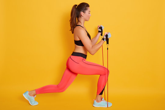 Indoor shot of strong woman dressed black bra and leggins, using resistance band in her exercising at home, fitness model workout isolatedbover yellow background. Strength and motivation concept.