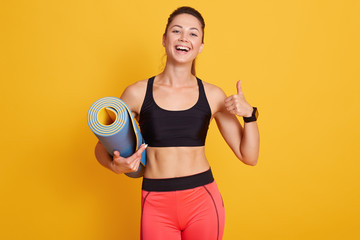 Image of slim beautiful woman ready for workout with yoga mat and thumbs up, sporty female looks laughing at camera and showing ok sign, dresses black bra and red leggins. Healthy lifestyle concept.